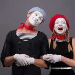 31769753 - waist-up portrait of mime couple with white faces, male mime looking at his partner, female mime happy smiling and looking at the camera isolated on grey background with copy place