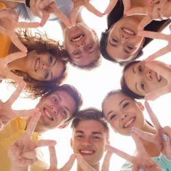 40534794 - friendship, youth, gesture and people - group of smiling teenagers in circle showing victory sign